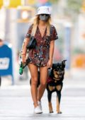 Emily Ratajkowski displays her long legs in printed board shorts and matching shirt while walking her dog in New York City