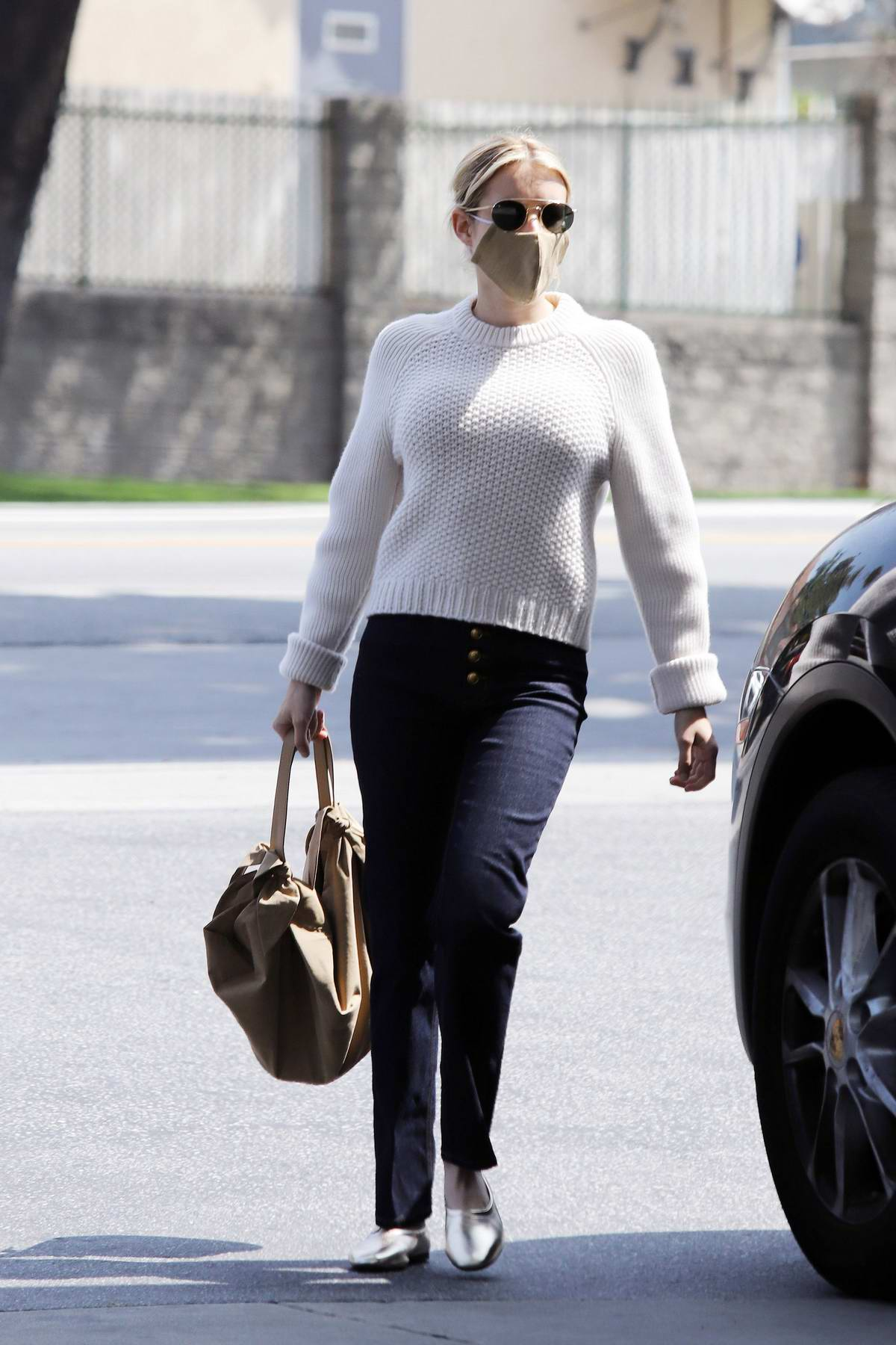 Emma Roberts seen wearing a white sweater and black jeans as she steps out in Los Angeles
