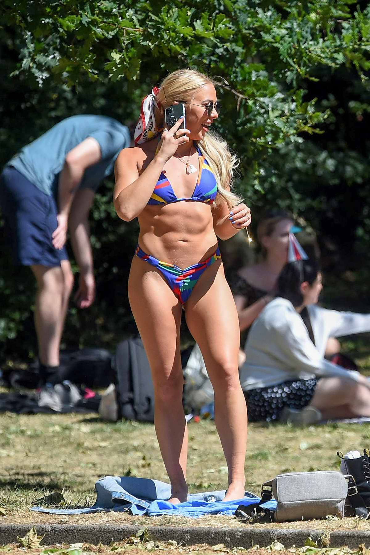 Gabby Allen slips into a colorful bikini while enjoying the sun with friends at a local park in London, UKith friends at a local park in London, UK