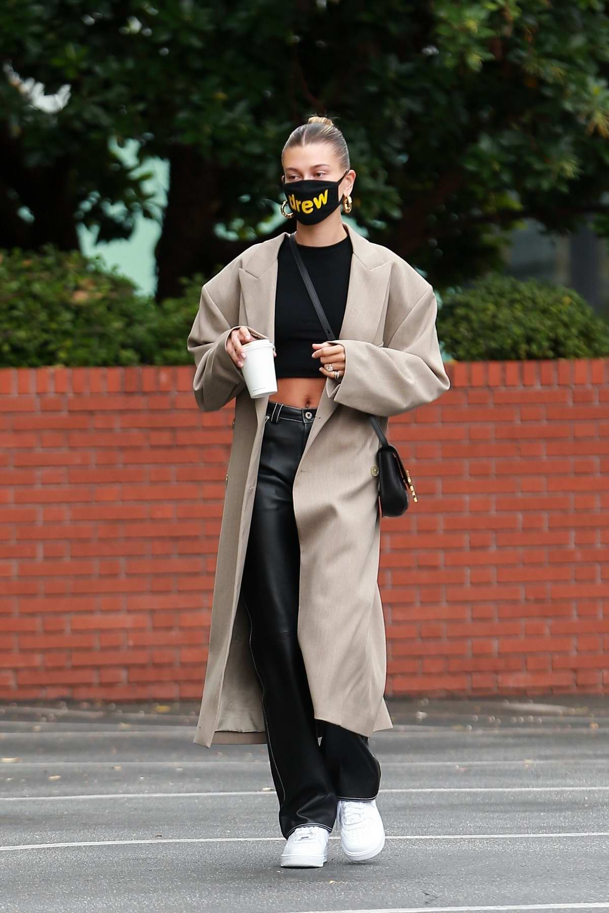 Hailey Bieber looks chic in a beige long coat and black leather pants during a coffee run in Beverly Hills, California