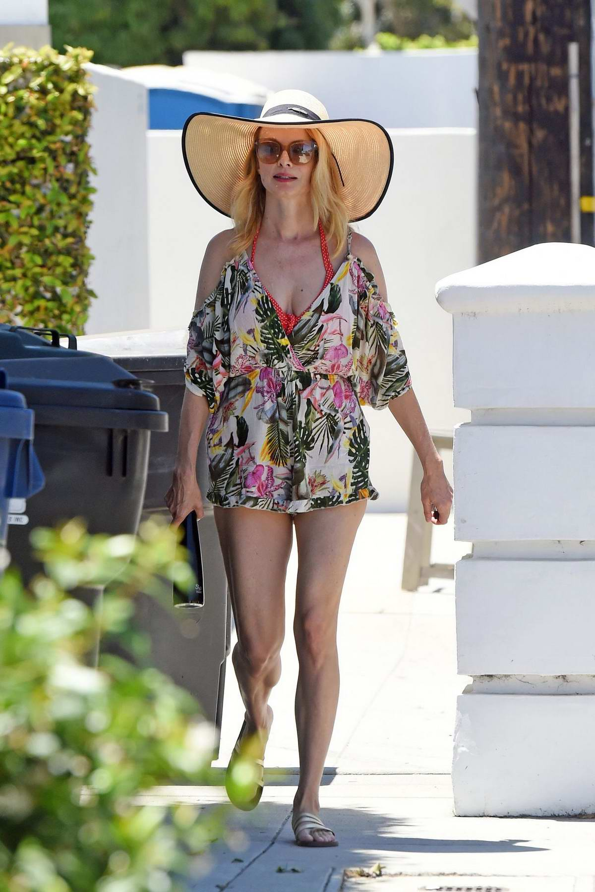 Heather Graham wears a floral romper with a large sunhat while visiting a beach house with friends in Malibu, California