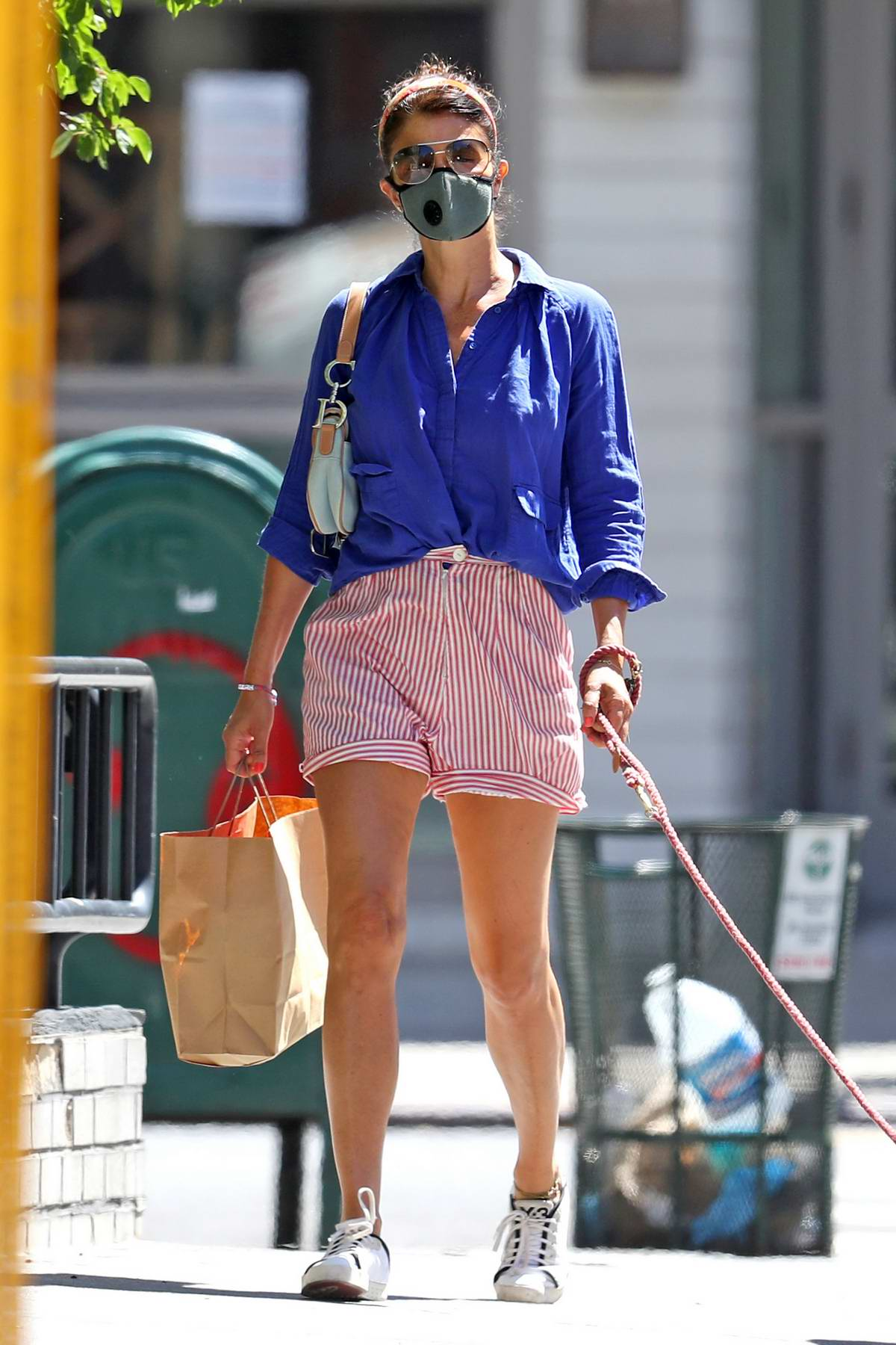 Helena Christensen looks stylish in navy blue shirt and striped pink shorts while out shopping with her dog in New York City