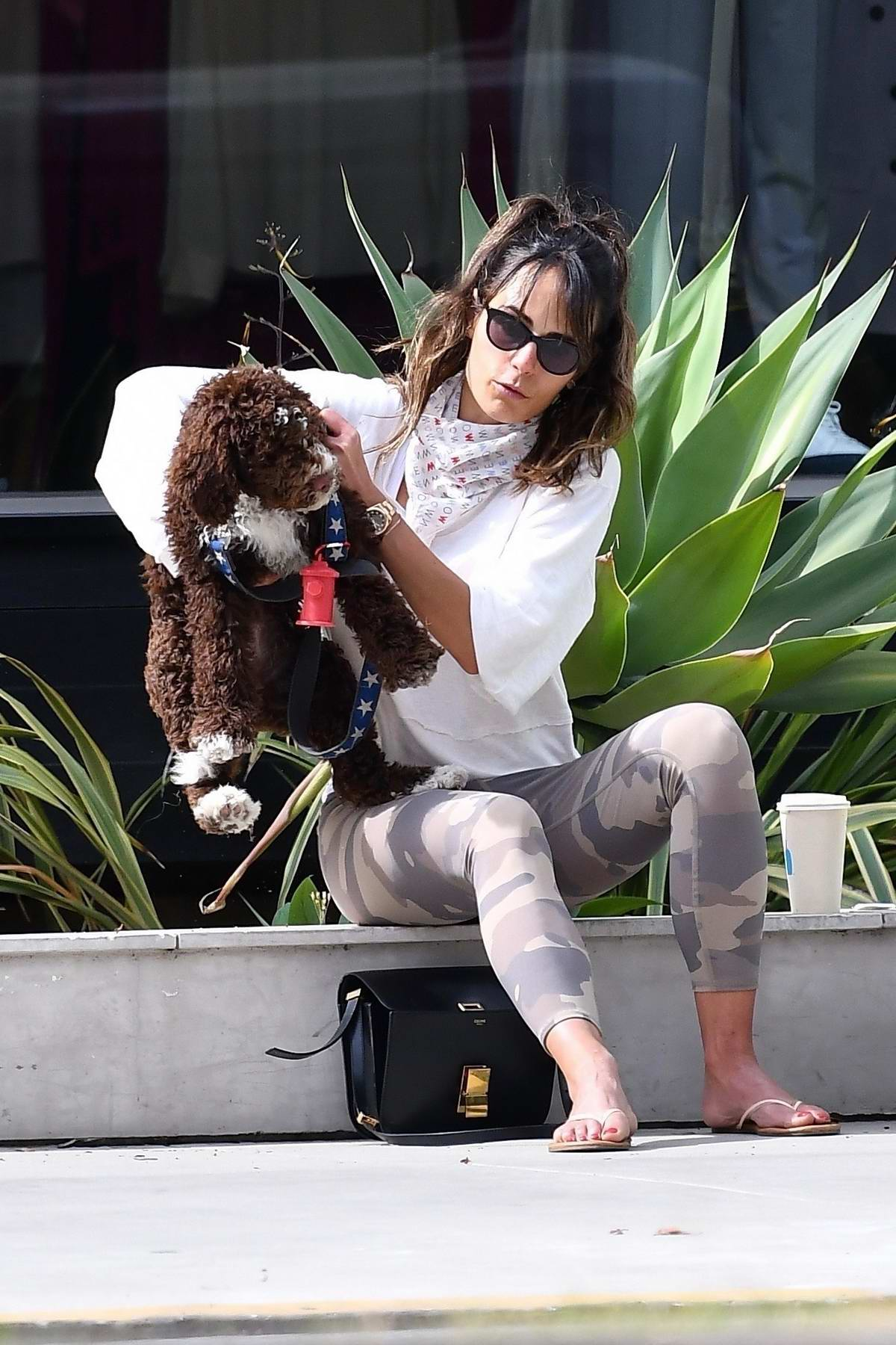 Jordana Brewster chats with a friend during a coffee run with her dog in Brentwood, California