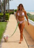 Kelly Bensimon wears a pink bikini as she walks her dog in Palm Beach, Florida