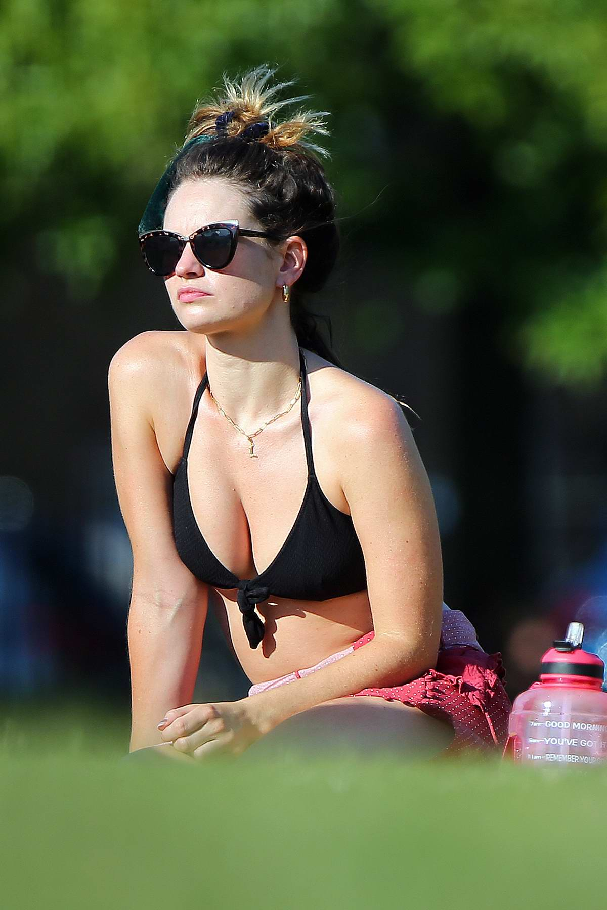 Lily James spotted in a black bikini top catching some sunshine at a park in London, UK