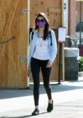 Nina Dobrev keeps it casual with an unbuttoned shirt, white top and black leggings while out running errands in Los Angeles