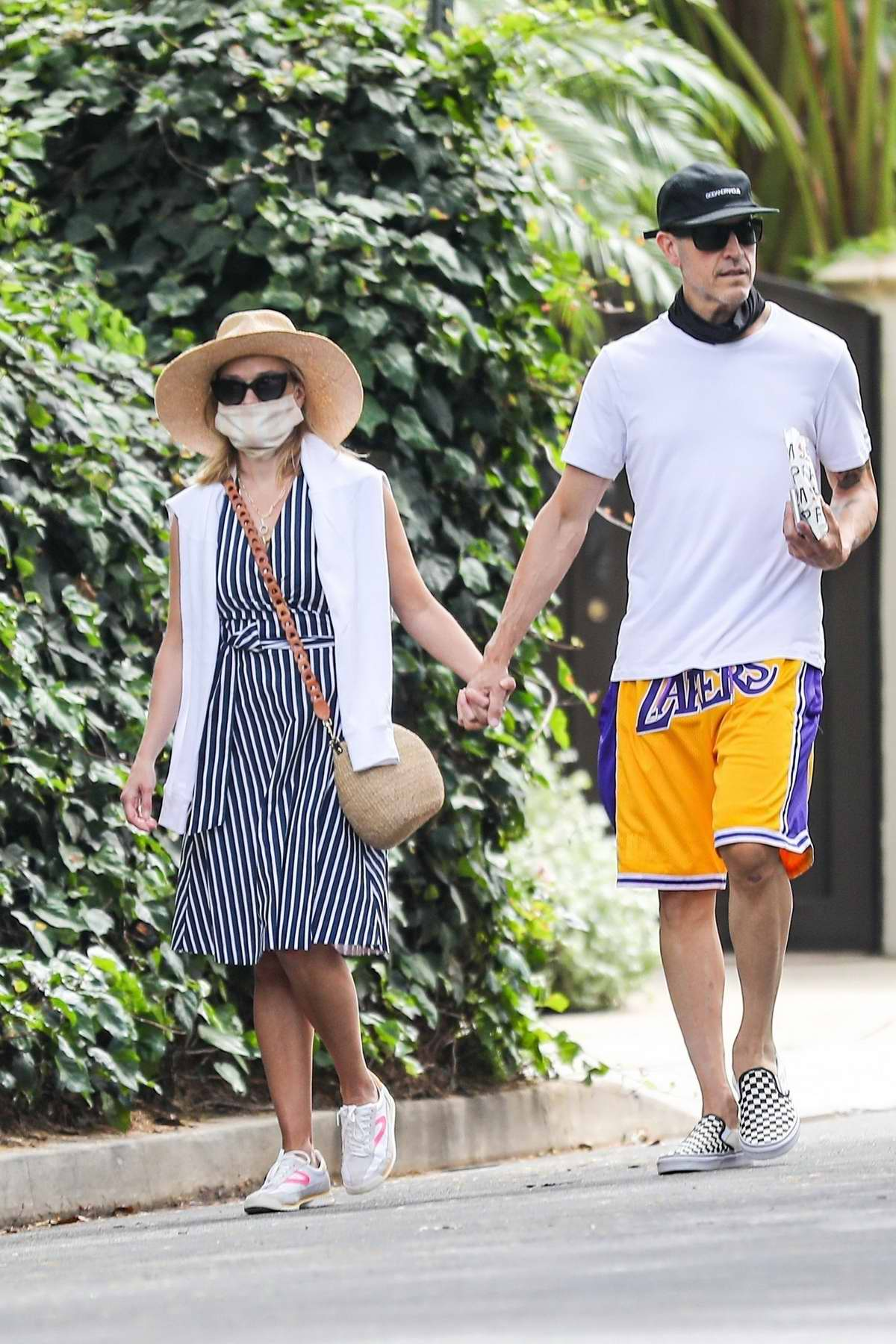 Reese Witherspoon and Jim Toth hold hands as they walk to the Farmshop in Brentwood, California