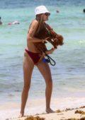 Roosmarijn de Kok seen wearing a maroon bikini as she hits the beach with her dog in Miami, Florida