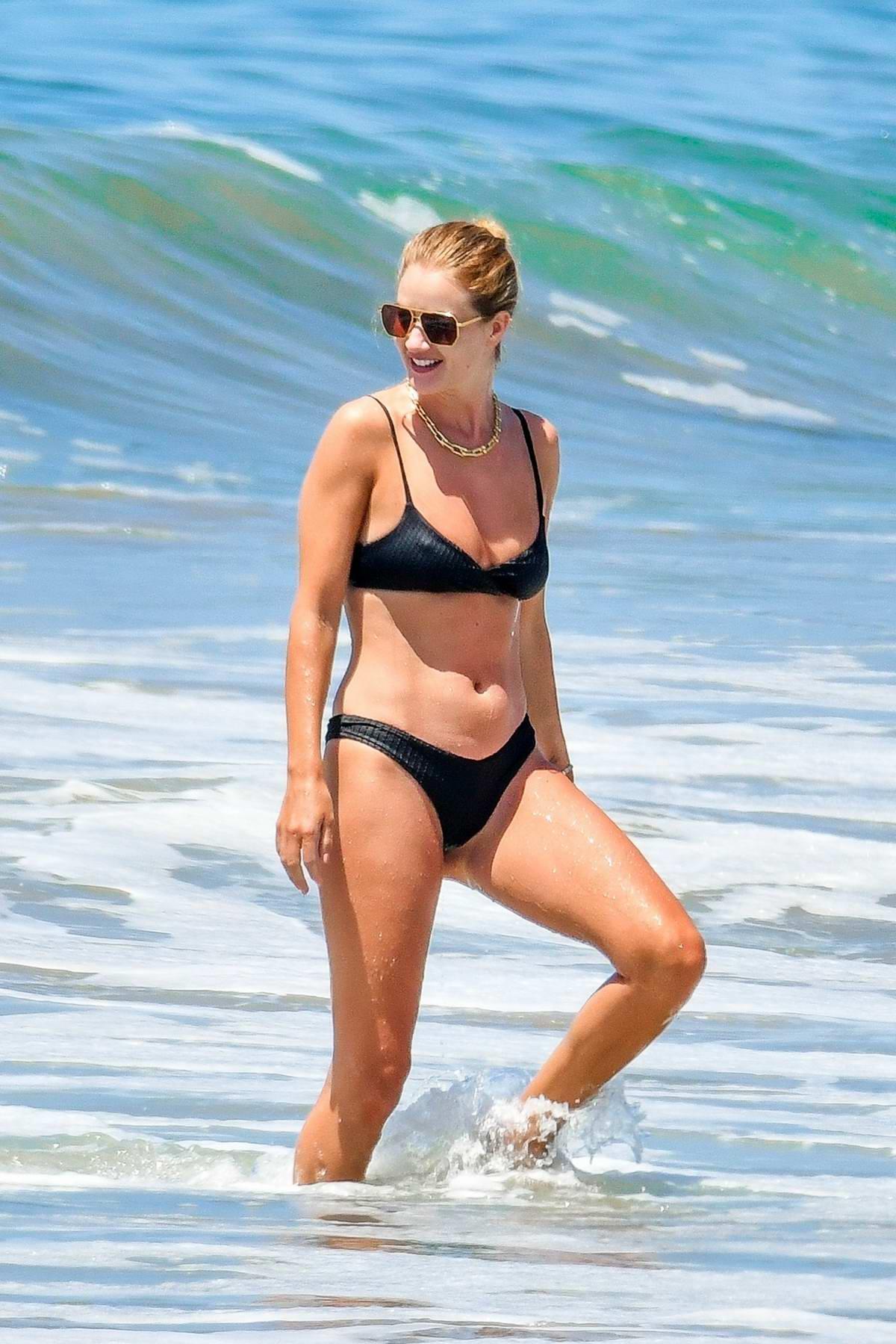 Rosie Huntington-Whiteley shows off her beach body in a black bikini as she hits the ocean in Malibu, California