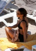 Alicia Vikander slips into a black bikini while enjoying some beach time with her friends in Ibiza, Spain
