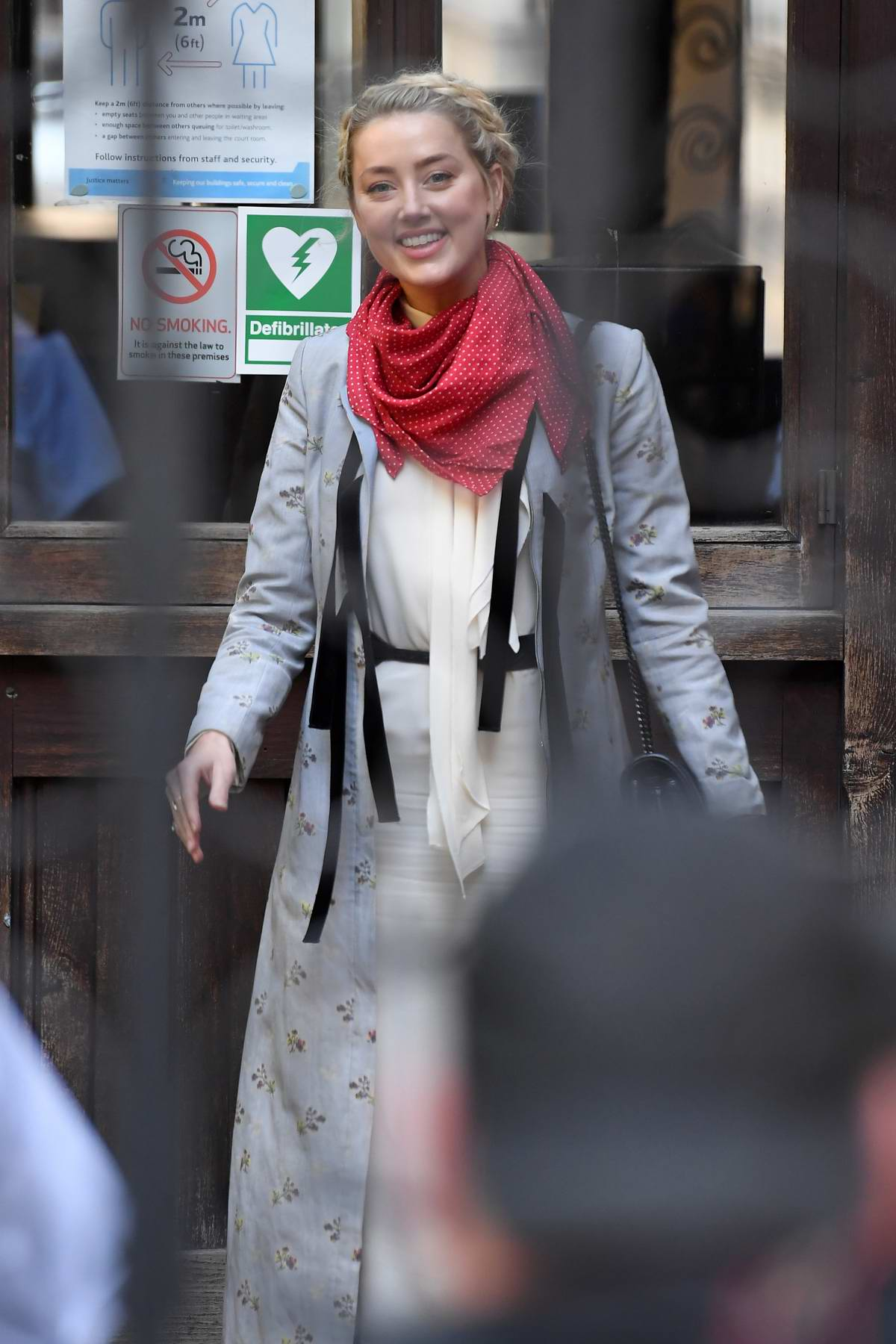 Amber Heard flashes a smile as she arrives at the Royal Courts of Justice in London, UK