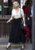 Amber Heard waves for the camera as she arrives at the Royal Courts of Justice in London, UK