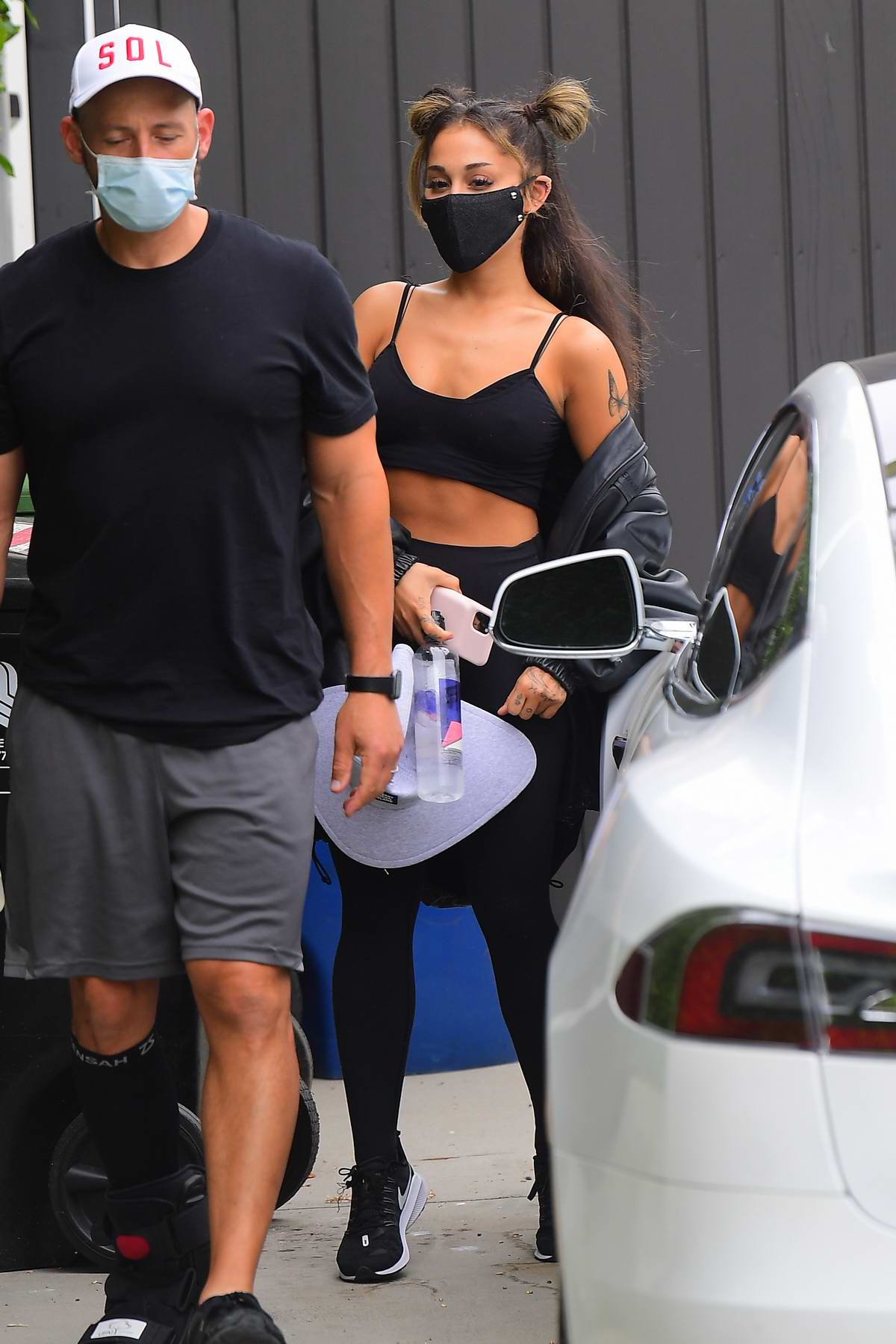Ariana Grande shows off her fit figure in a crop top and leggings as she leaves the gym in Los Angeles