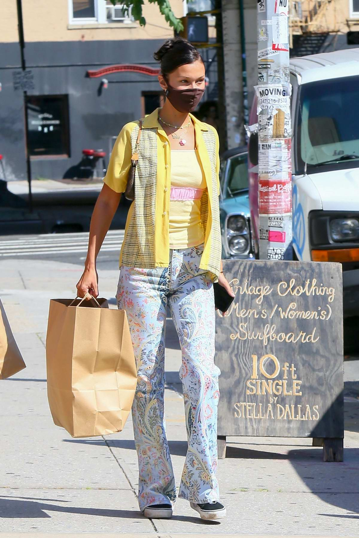 Bella Hadid wears a yellow shirt and paisley print denim while out for shopping with a friend in Brooklyn, New York