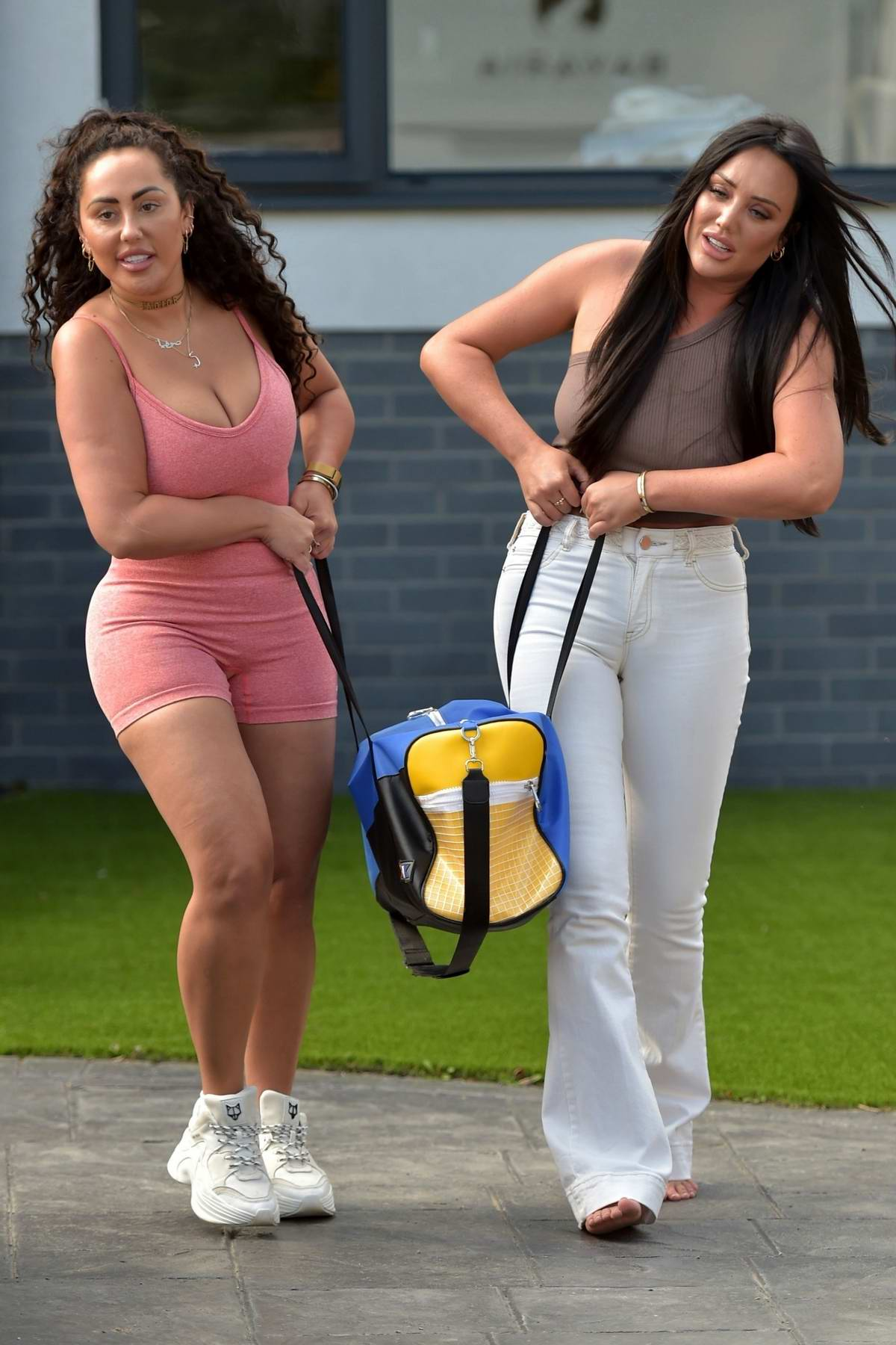 Charlotte Crosby and Sophie Kasaei struggle with their luggage as they leave for Ibiza, Spain