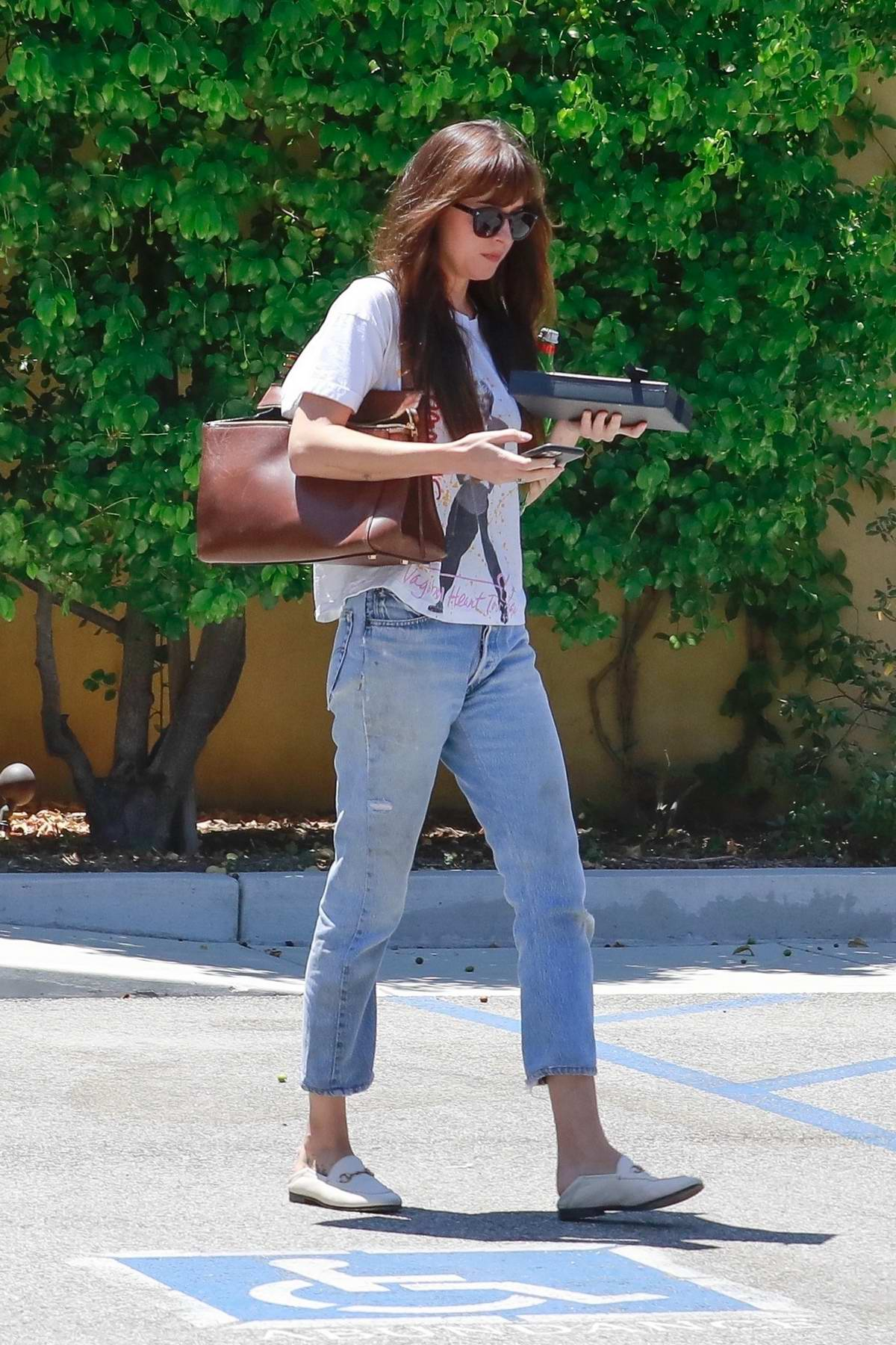 Dakota Johnson dons a simple tee and jeans while paying a visit to her doctor in Los Angeles