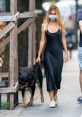 Emily Ratajkowski looks stunning in a black satin dress as she steps out to walk her dog in New York City