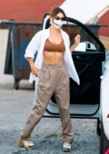 Emily Ratajkowski rocks a white shirt over a sports bra while heading out with a friend in New York City