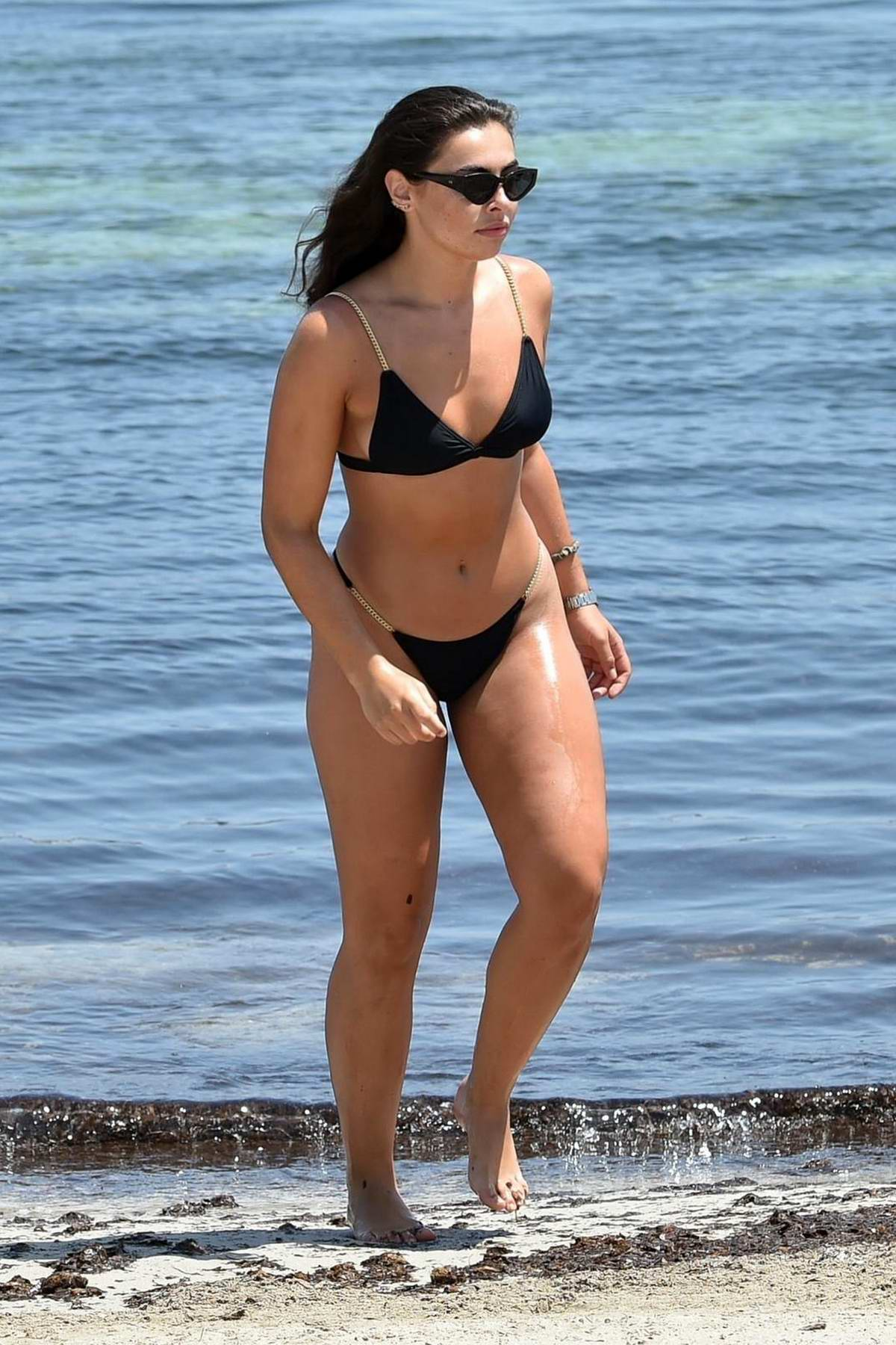 Francesca Allen wears a black bikini while enjoying a day on the beach with her friend Lucy May in Ibiza , Spain