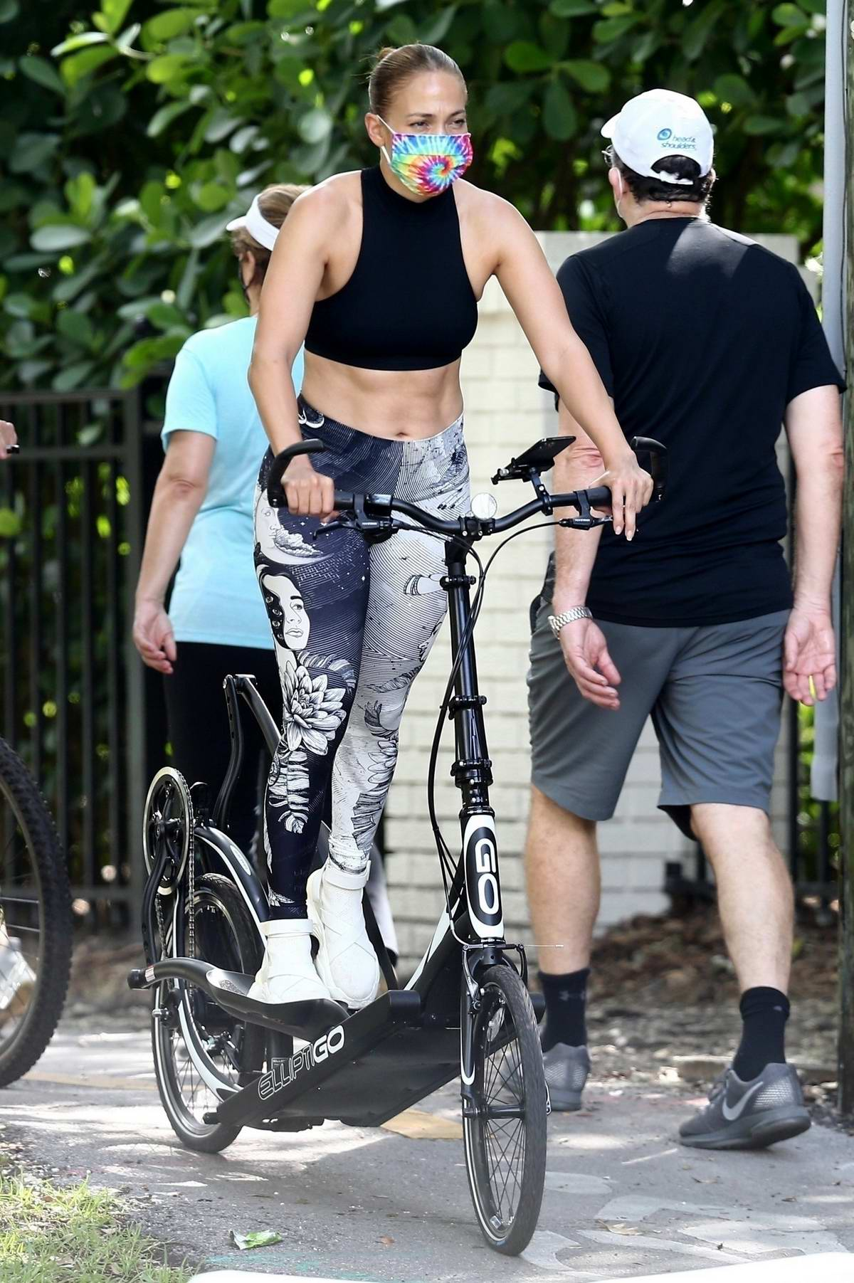 Jennifer Lopez wears a black crop top and printed leggings as she gets in a workout on her ElliptiGo bike in Miami, Florida