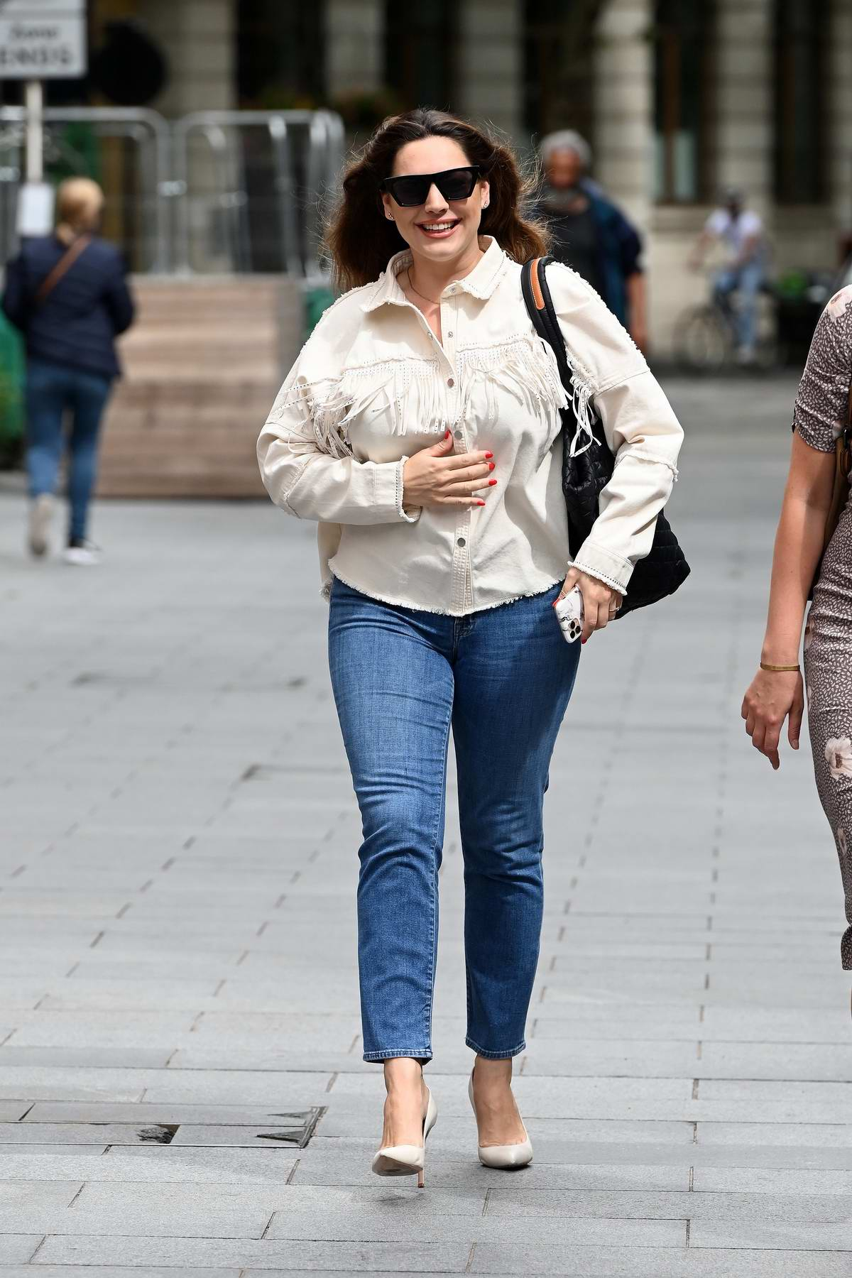 Kelly Brook is all smiles as she leaves Global Radio with a colleague in London, UK