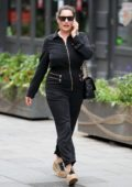 Kelly Brook looks animated during phone call wearing black boiler suit in London, UK