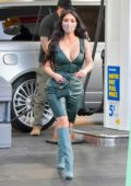 Kim Kardashian rocks green leather outfit with matching knee-high boots as she makes stop at gas station in Los Angeles