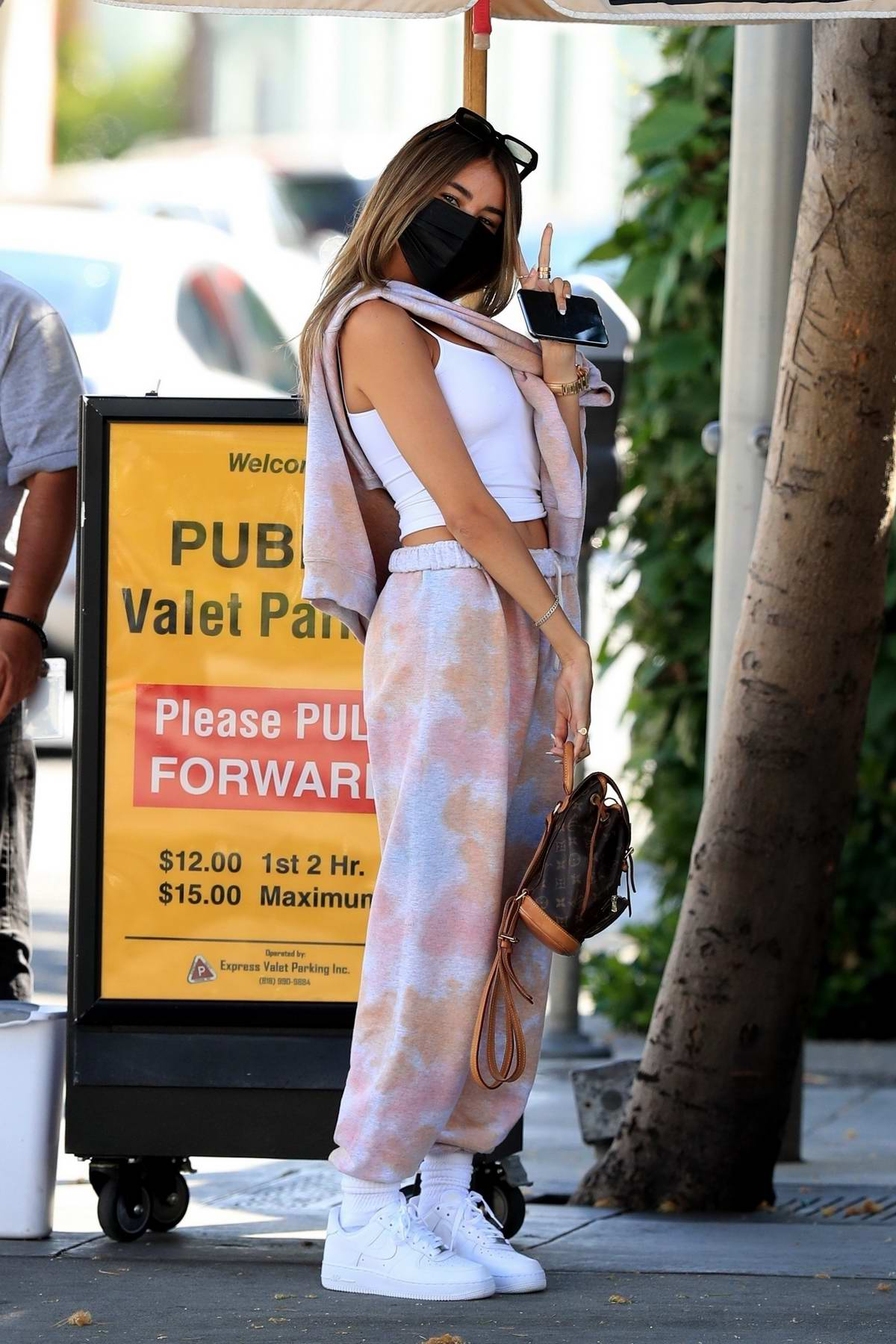 Madison Beer seen waiting for her ride after lunch with a mystery man at Il Pastaio in Beverly Hills, California