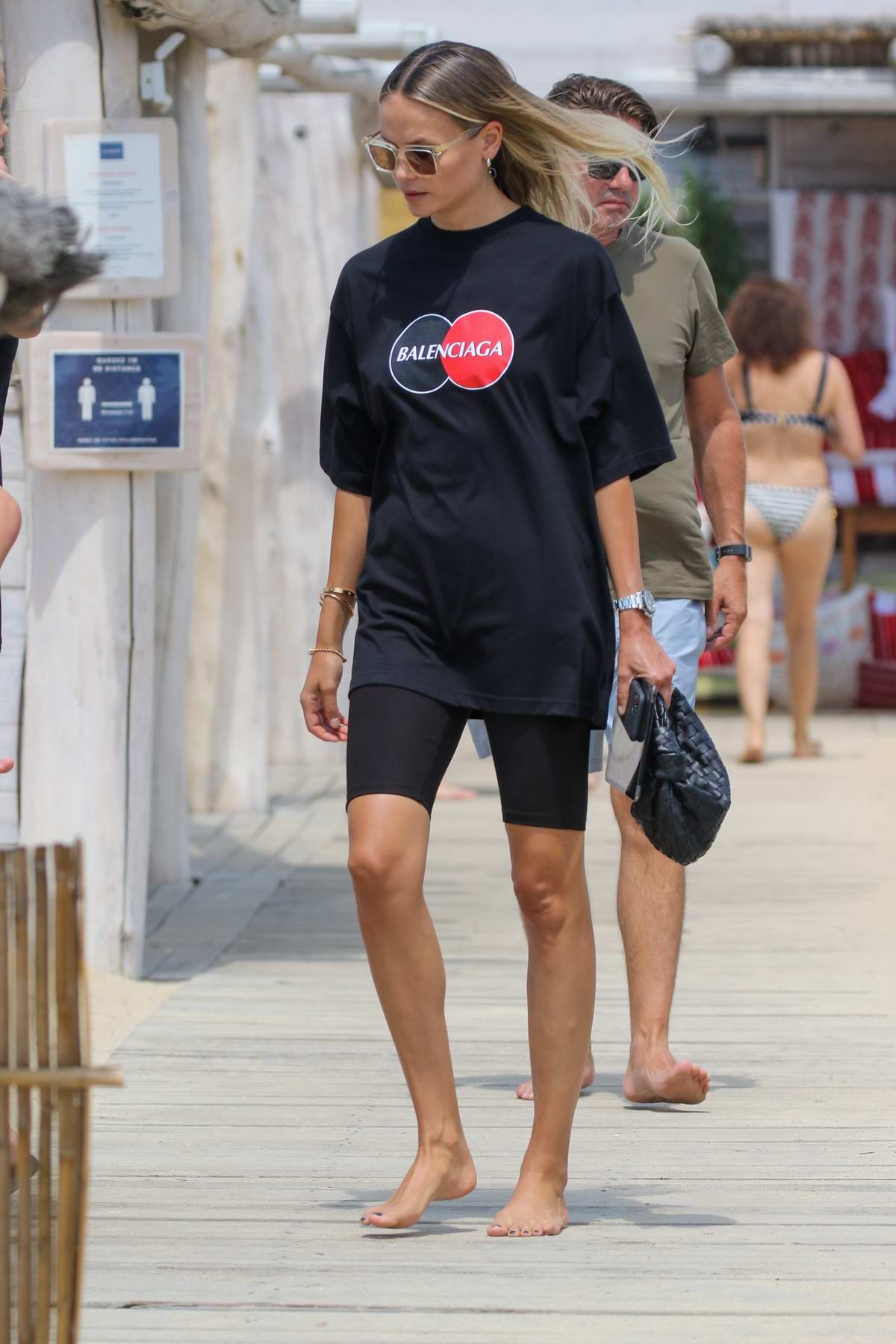 Natasha Poly wears an oversized black Balenciaga tee and bike shorts as she arrives at the Club 55 Beach in Saint-Tropez, France