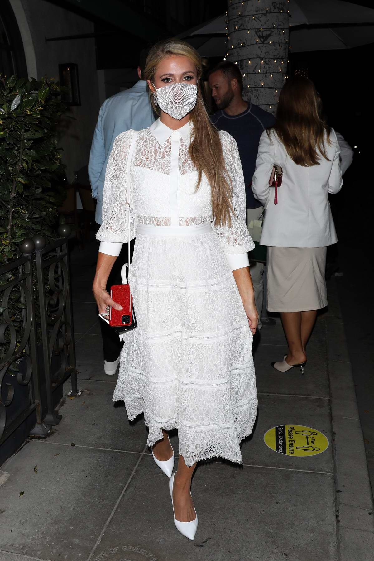 Paris Hilton looks great in a white dress as she grabs dinner with friends at Madeo restaurant in Beverly Hills, California