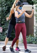 Reese Witherspoon sports a grey tank top and red leggings while out for a walk with a friend in Santa Monica, California