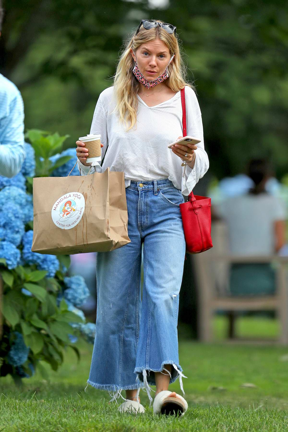 Sienna Miller wears a white top and flared jeans as she steps out for a coffee in The Hamptons, New York