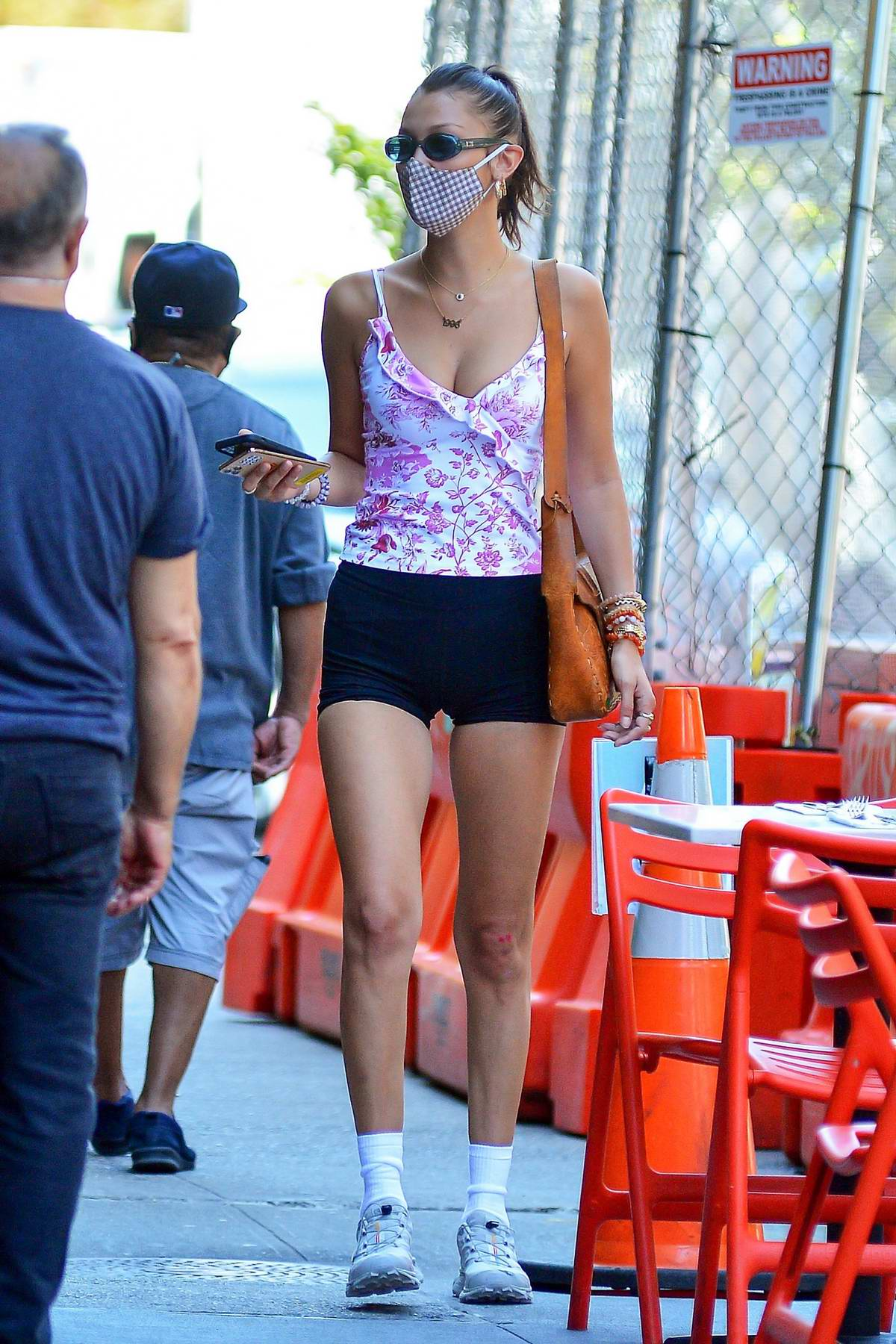 Bella Hadid flaunts her amazing figure in a floral print top and black shorts as she arrives at Bar Pitti in New York City
