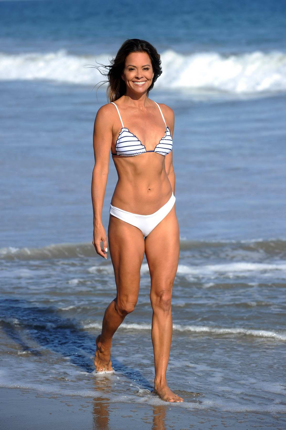 Brooke Burke seen wearing a white bikini while filming for her fitness app at the beach in Malibu, California
