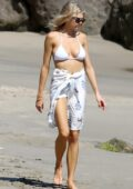 Charlotte Mckinney seen wearing a white bikini while catching some sun at the beach in Los Angeles