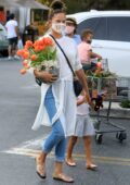 Chrissy Teigen shows her growing baby bump while picking up flowers and grocery shopping in Los Angeles