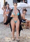 Demi Rose stuns in a blue bikini as she enjoys a healthy smoothie while out on the beach in Ibiza, Spain