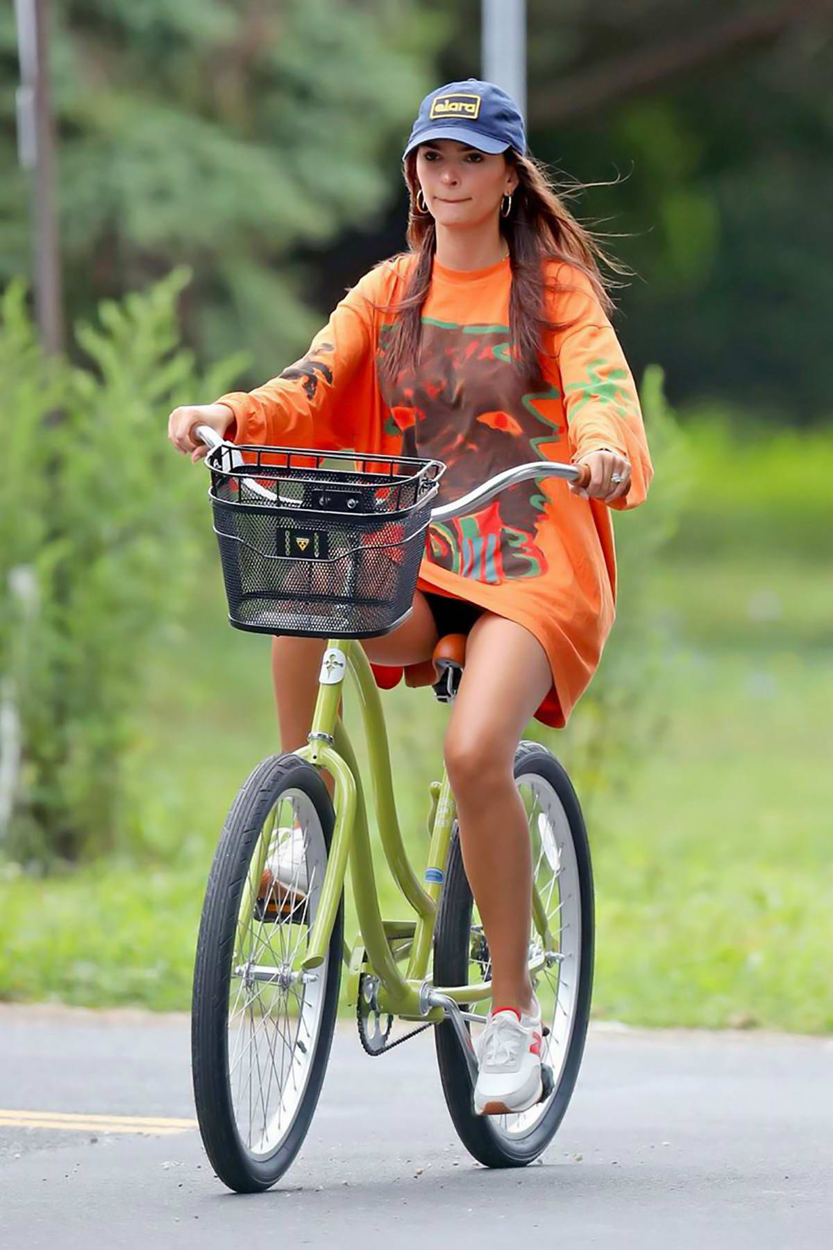 Emily Ratajkowski dons an oversized orange sweatshirt while out for a bike ride in The Hamptons, New York