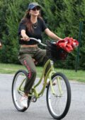 Emily Ratajkowski rides her bike to the beach with friends in the Hamptons, New York
