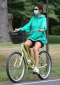 Emily Ratajkowski wears a green hoodie and shorts while out for a bike ride in the Hamptons, New York