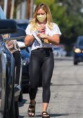 Hilary Duff wears a white crop top and black leggings while making a stop at a Starbucks in Malibu, California