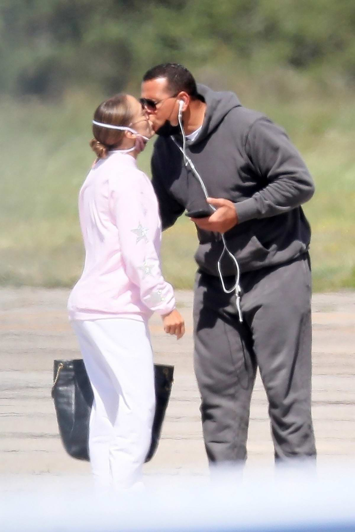 Jennifer Lopez and Alex Rodriguez share a kiss at a private airport while leaving the Hamptons, New York