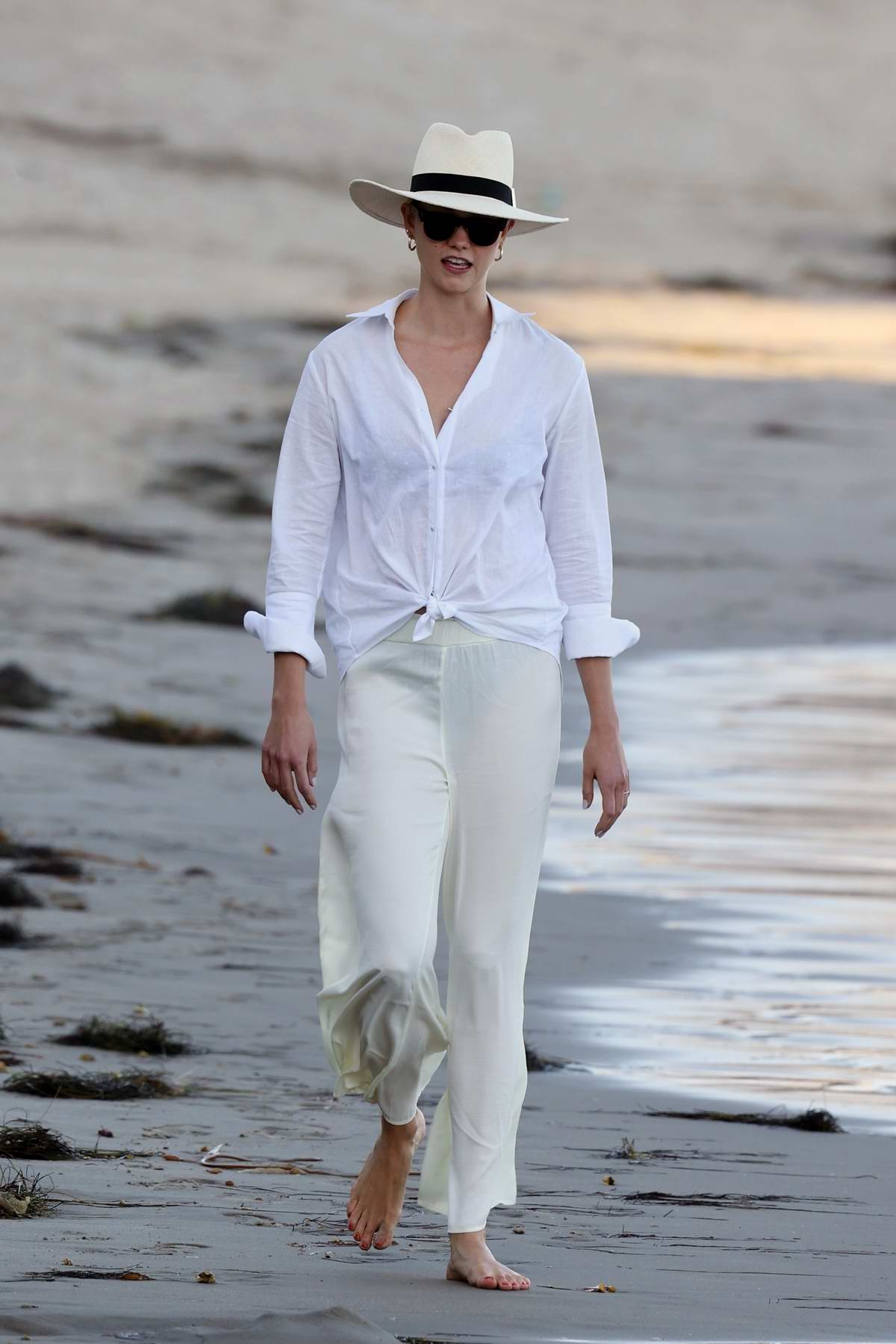 Karlie Kloss wears a stylish white ensemble as she walks the beach with her friends in Santa Monica, California