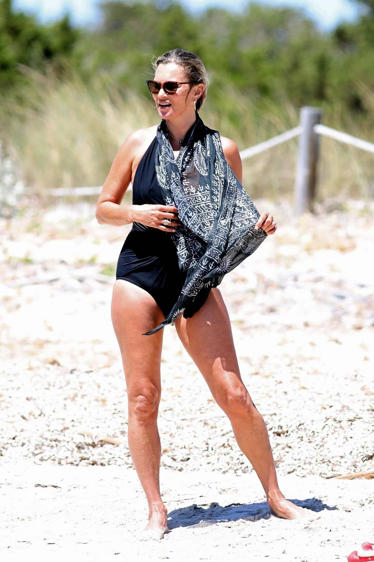 Kate Moss spotted in a black swimsuit while on the beach during a summer holiday in Formentera, Spain