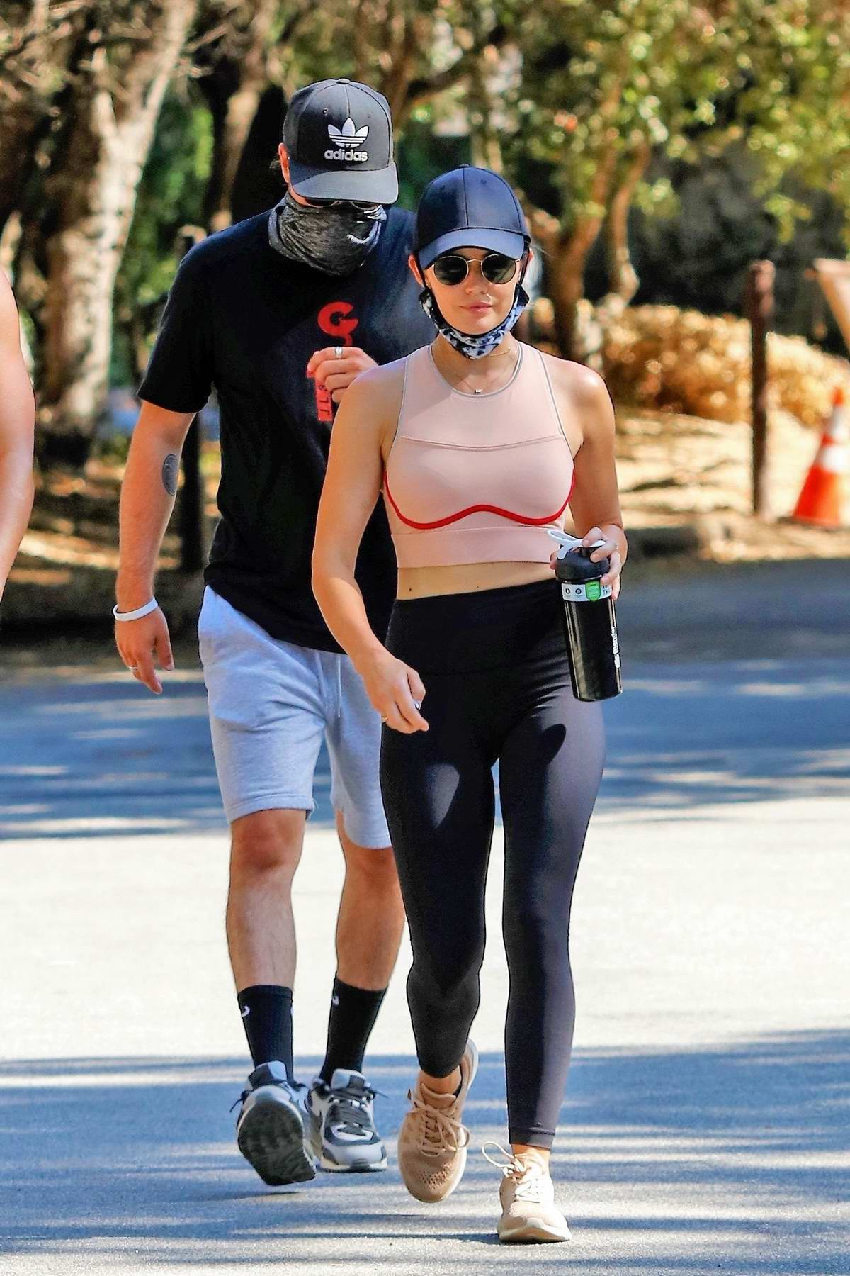 Lucy Hale sports a pink workout top and black leggings during an afternoon hike with friends in Studio City, California