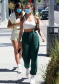 Madison Beer wears white crop top and green sweatpants for a lunch outing with a friend in Beverly Hills, California