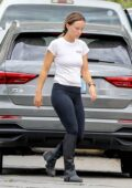 Olivia Wilde clears her driveway by moving her trash cans as she arrives home after horse riding in Los Angeles