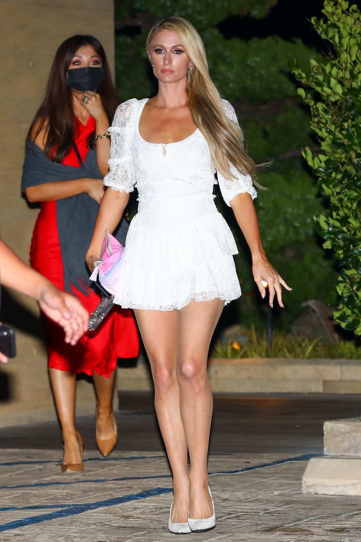 Paris Hilton flaunts her long legs in a white mini dress during a dinner outing at Nobu in Malibu, California
