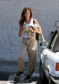 Rainey Qualley uses her sweatshirt as a makeshift mask as she stops by her local 7-Eleven store in Los Angeles