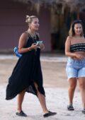 Rita Ora reveals her black bikini while wearing a black dress as she leaves Sunset Ashram in Ibiza, Spain